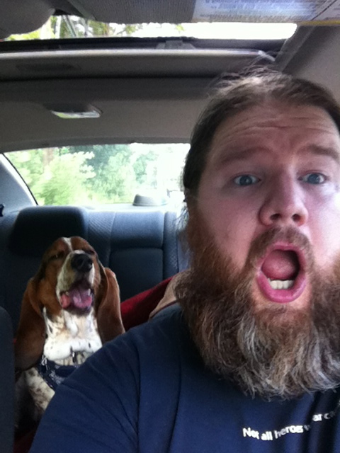 man singing with mouth open in car with dog